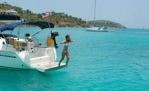 Photo of a charter yacht in Antigua with girl jumping off the back into the CAribbean sea